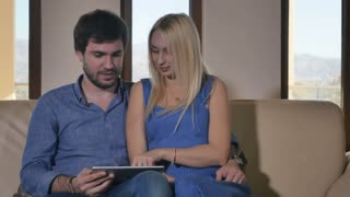 Young couple using a tablet on the sofa