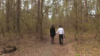 Young couple walking in the forest and holding hands