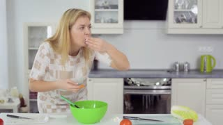 Young fat woman greedily eats a pieces of salad while no one sees her