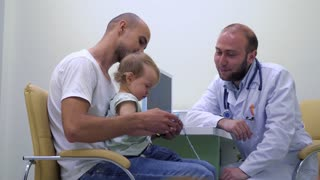 Young father with little daughter at the pediatrician consultation