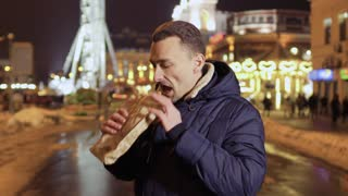 Young funny guy enjoys a smell of street food