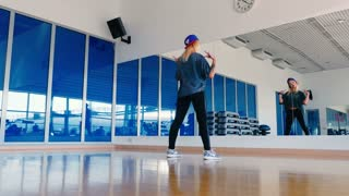 Young girl in cap dancing hip-hop in front of the mirror in gym