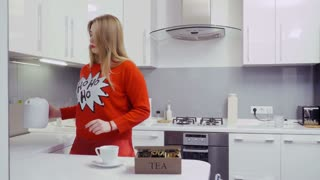 Young girl in red sweater makes tea at the kitchen