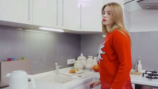 Young girl in red sweater making tea at the kitchen
