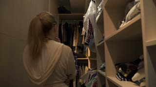 Young girl look for a clothing in dressing room at home