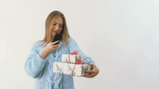 Young girl makes a photo of festive presents at white background