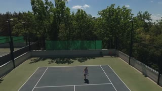Young girl play tennis outdoors at the tennis court