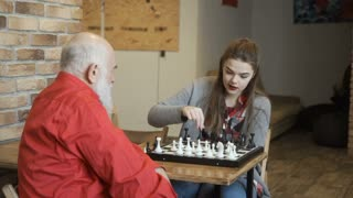 Young girl plays chess with grandfather