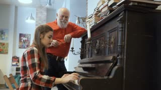Young girl plays the piano for grandfather