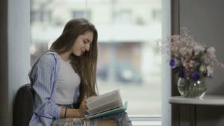 Young girl read the book sitting at window sill