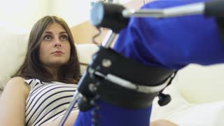 Young girl recovery her injured leg at passive mechanotherapy apparatus