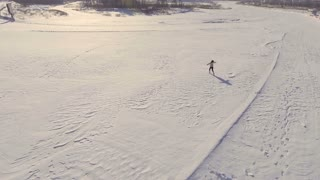Young girl runs through open space at the winter, aerial view