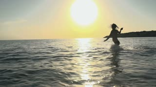 Young girl splashes the water in the ocean
