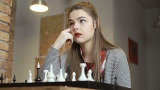 Young girl thinks about the next move during chess game