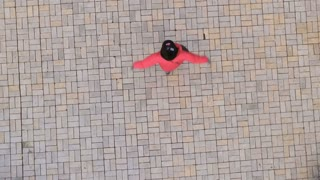 Young girl wearing red jacket circles on the ground, shooting from drone