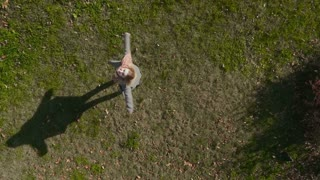 Young girl whirling at green grass, shooting from drone