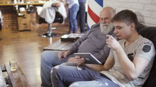 Young guy and mature man uses digital tablet and waits their turns in barbershop