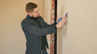 Young guy choose the color for a walls in new apartment