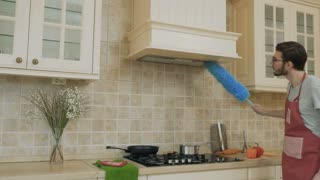 Young guy clean kitchen with duster and cooking soup on stove