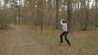 Young guy fighting with stick in virtual reality glasses in the forest