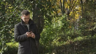 Young guy in coat searches a signal of network on his smartphone in park