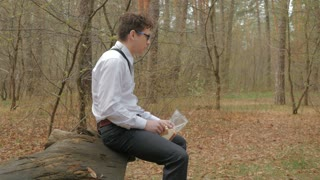 Young guy in glasses relaxing in the forest and eating the sandwich