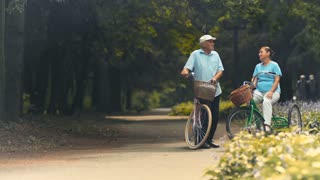 Young guy invites old couple on bicycles to ride with him in park