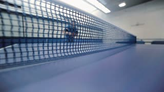 Young guy playing table tennis across the tennis net