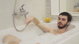 Young guy relax in the bath with foam