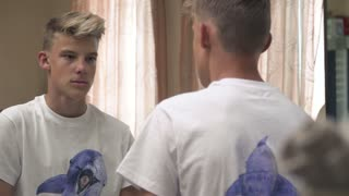 Young guy wipes his face in front of a mirror