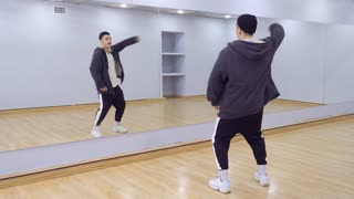 Young handsome guy dances in front of the mirror