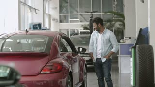 Young happy couple bought a car in car showroom