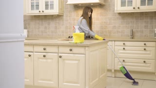 Young housewife cleans kitchen floor with mop
