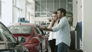 Young in love couple choose the automobile in car showroom