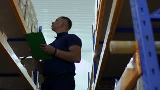 Young inspector check boxes in warehouse and writing report