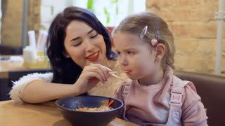 Young korean feeds her little daughter with a noodles in restaurant