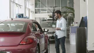 Young man and woman just bought a car in car showroom