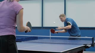 Young man and woman playing a table tennis