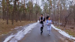 Young man and woman runs together in the winter forest