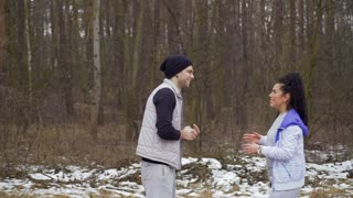 Young man and woman talks in winter forest
