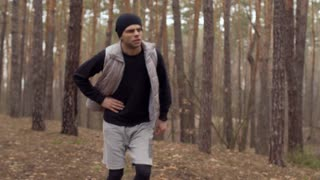Young man has a pain in his stomach during running in the forest
