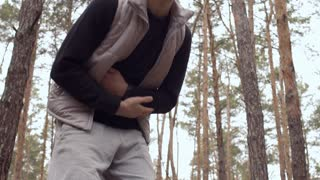 Young man has pain in stomach during training in the forest