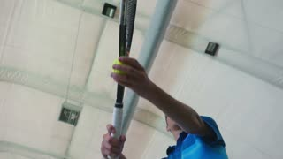 Young man hit the tennis ball with racket in close-up