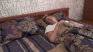 Young man is sleeping in the bed