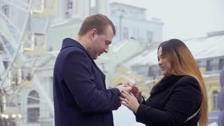 Young man makes marriage proposal to beautiful woman in the amusement park