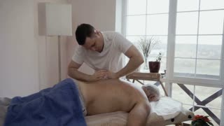 Young man makes massage to senior man