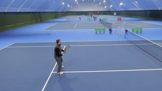 Young man play tennis, view from flying drone