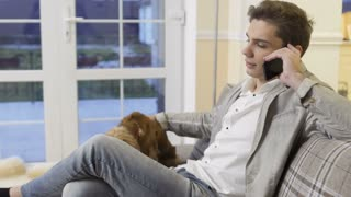 Young man relax at home on sofa talking on the phone and strokes his dog