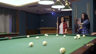 Young man show his girlfriends how to hit the balls in billiard game