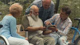 Young man shows to elderly people how to use tablet